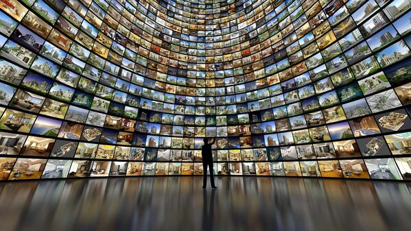 Person standing in front of a wall of hundreds of square images