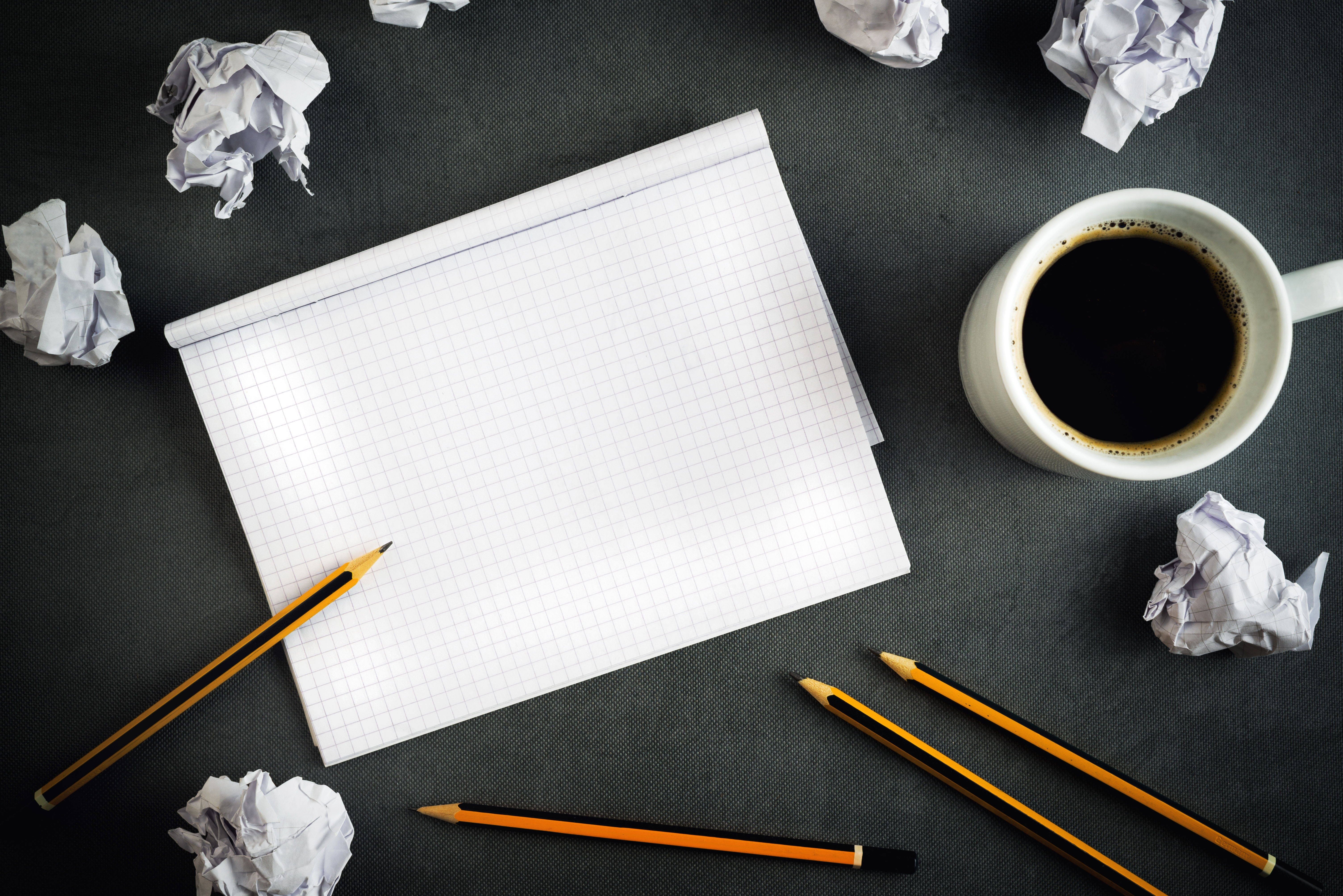 Crumpled paper, coffee and a blank sheet of paper - an all too familiar indicator of writer's block.