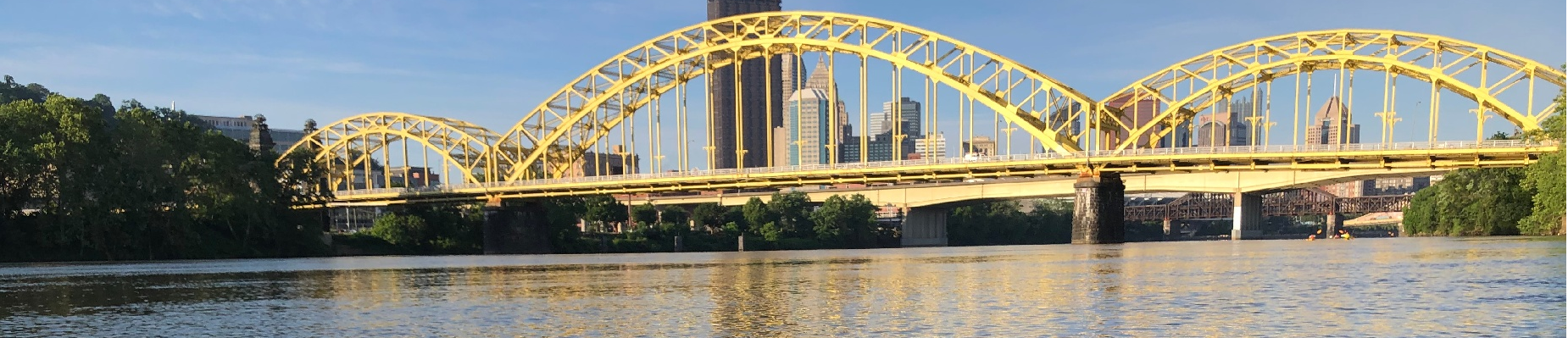 Yellow bridge with Pittsburgh skyline in the background during the day