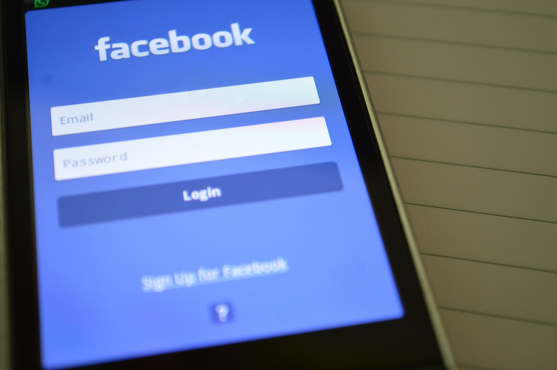 The Facebook login page on the screen of a mobile phone.