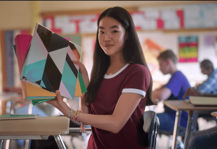 Girl in classroom holding binders.